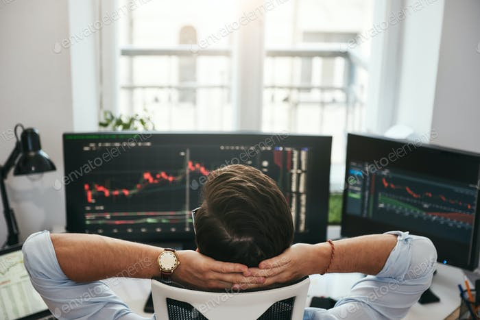 Time to relax. Back view of young businessman or trader holding hands behind head while looking at