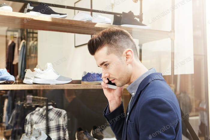 handsome man standing outside store window on phone call
