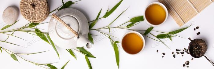 Asiatischer Hintergrund mit grünem Tee, Tassen und Teekanne mit Bambuszweigen