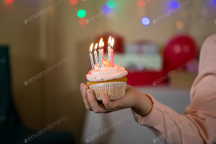 Girl holding cupcake with lit candle during birthday party