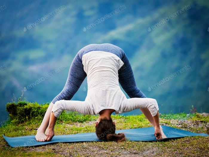 Frau tut Ashtanga Vinyasa Yoga Asana Prasarita padottanasana