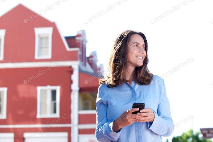 glückliche ältere Frau draußen mit Handy