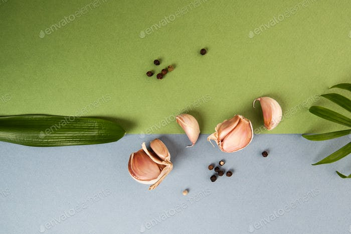 Garlic cloves on a blue-green textured background with tropical