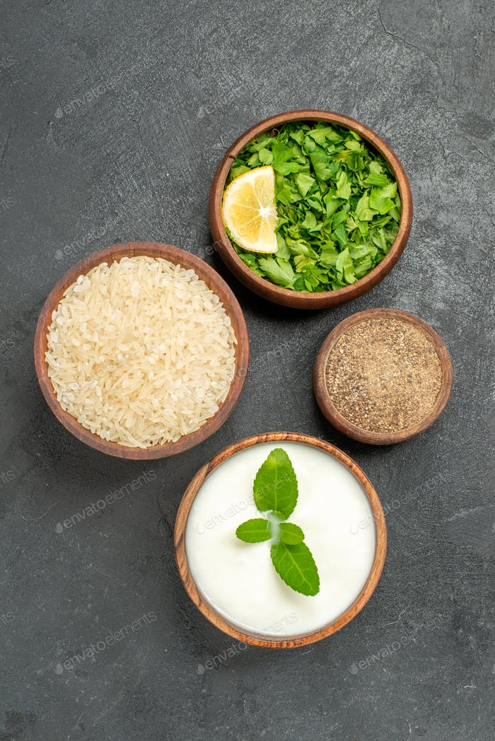 top view bowls with rice natural yogurt parsley pepper on dark background