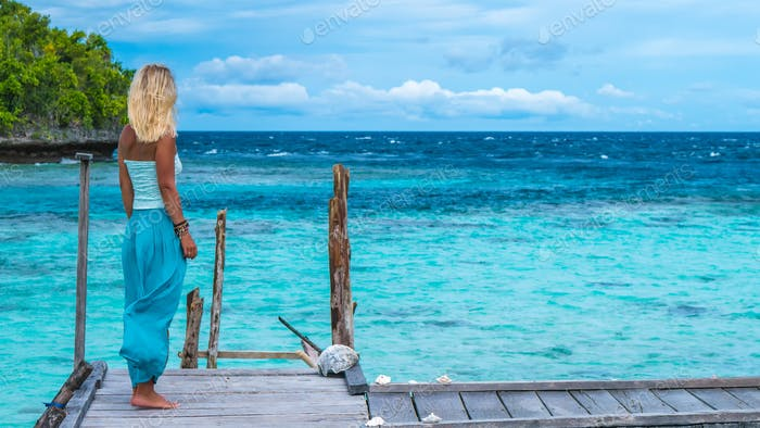 Blond Girl Staying on Wooden Pier of an Homestay looking into blue ocean, Gam Island, West Papuan