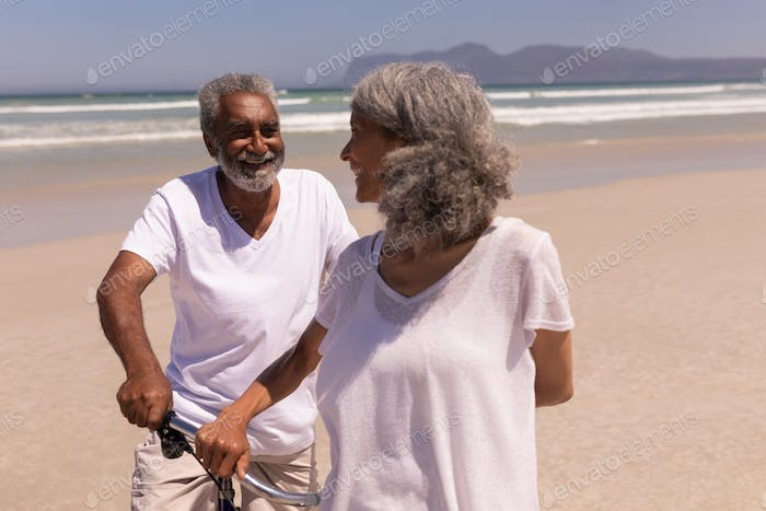 Happy senior couple standing with bicycle on beach in the sunshine