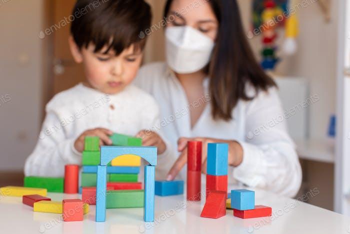 Niño jugando con bloques de madera y educador maestro ayuda a usar mascarilla para la pandemia de coronavirus.