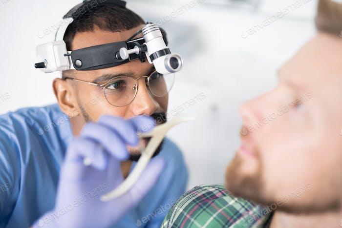 Junger Arzt in Handschuhen und Uniform gehen, um krankes Ohr des Patienten zu untersuchen