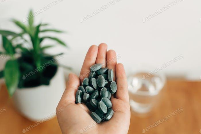 Hand hält Chlorophyll Tablette über Glas Wasser