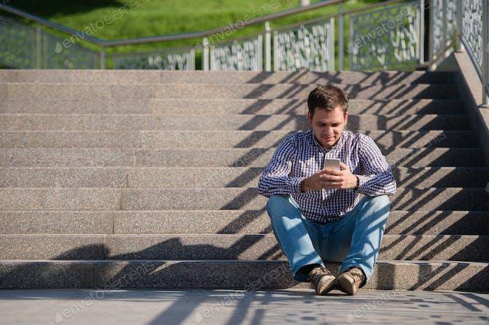 Menschen, Stil, Technologie und Lifestyle - junger Mann mit Smartphone sitzt auf der Treppe in der Stadt