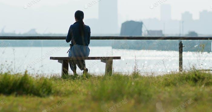 Frau genießen Sie das Meer und sitzen auf der Bank