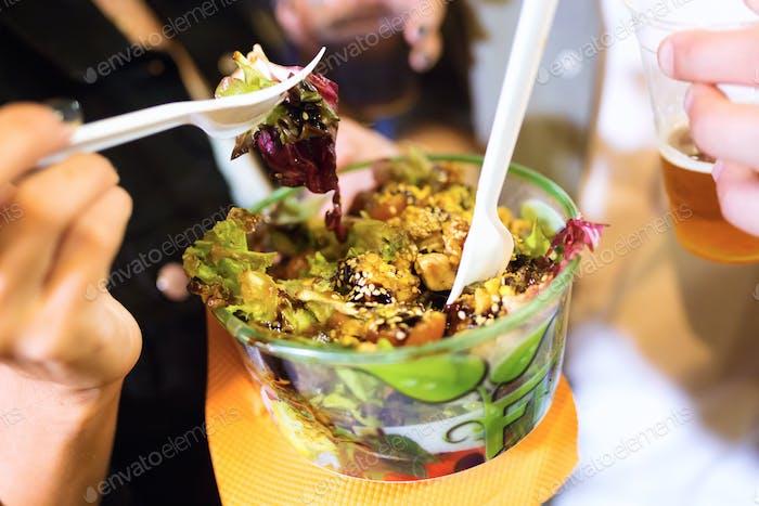 Junge Frau Besuch Essen Markt und essen bunte Salat auf der Straße.