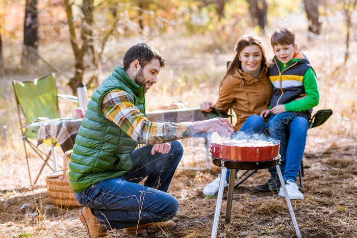 Happy family grilling meat on barbecue grill in autumn park