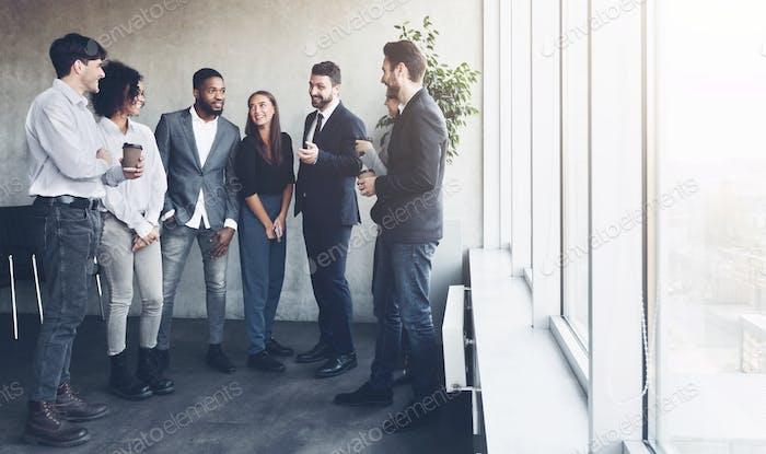 Business colleagues having coffee break near window