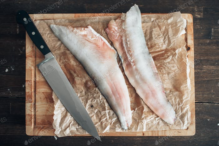 Raw fish slices, knife on cutting board, top view