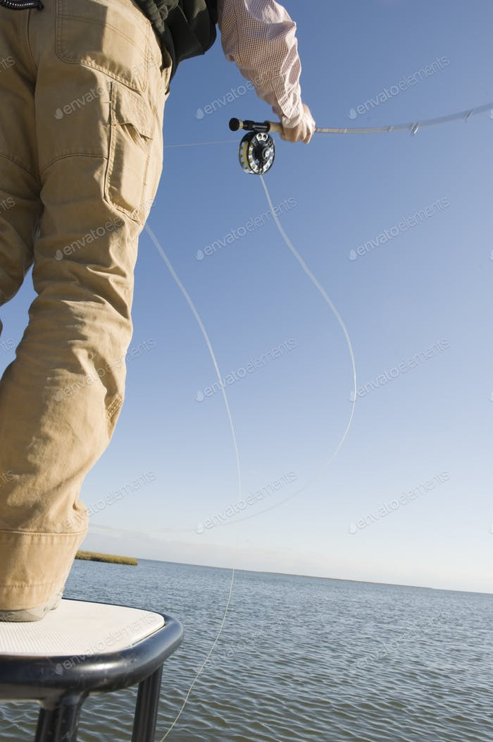 A closeup of a fly fisherman casting for redfish and tarpon in the marsh near New Orleans,