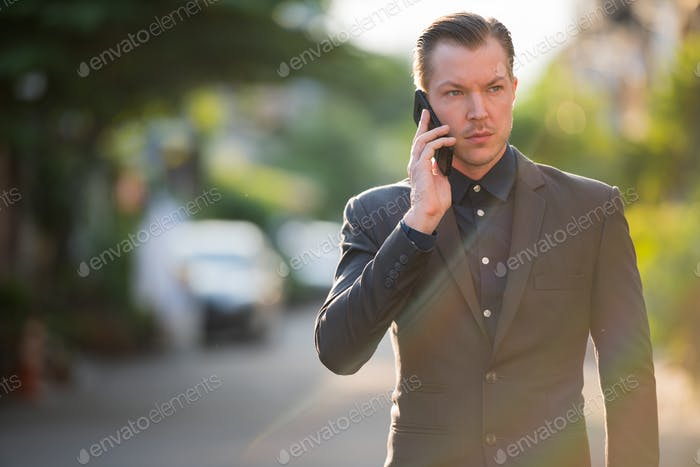 Portrait of young handsome businessman talking on the phone outdoors