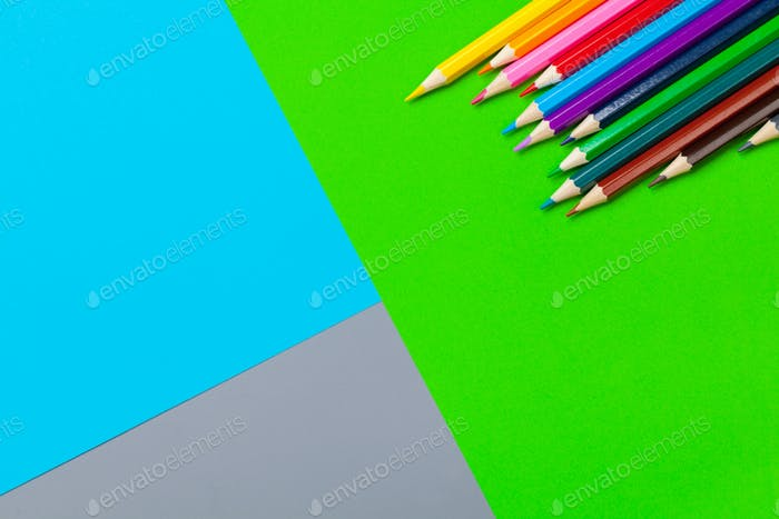 Colored pencils on bright color paper background