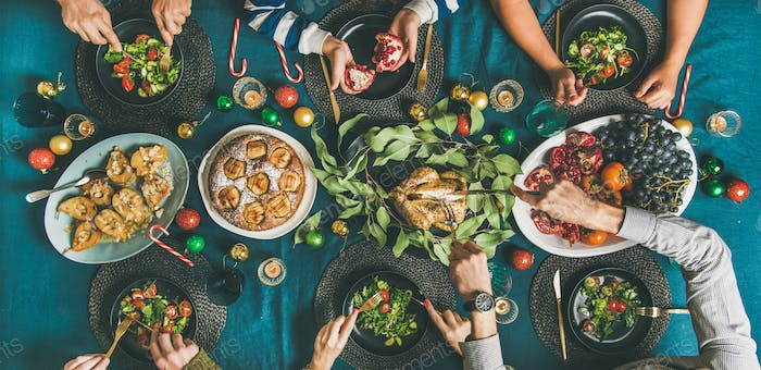 Human hands eating different meals at Christmas party dinner