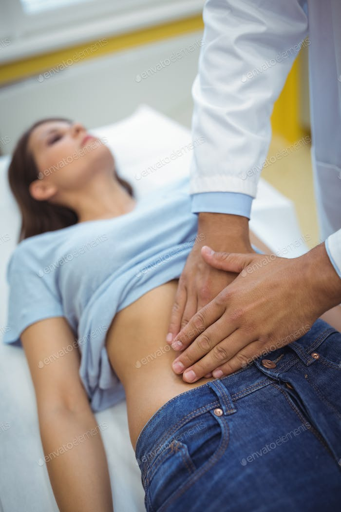 Doctor examining the stomach of a female patient