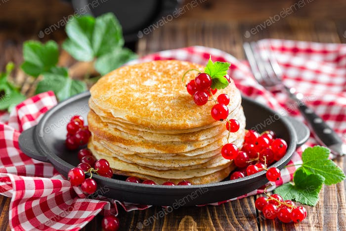 Thin french crepes stacked with fresh berries on wooden rustic table, closeup