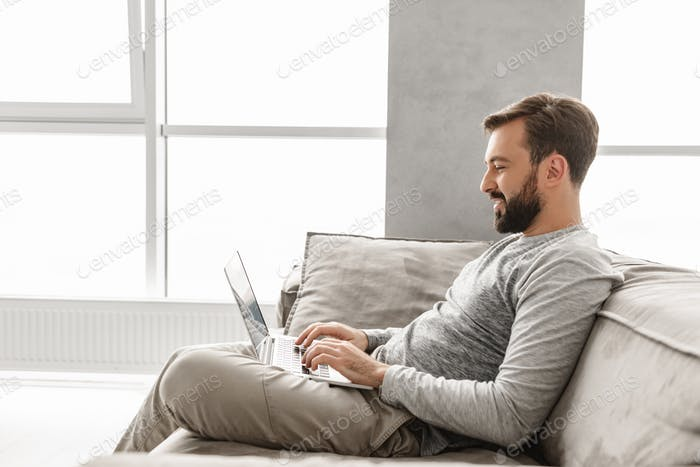 Portrait of a smiling young man working on laptop