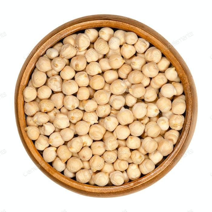 Dried chickpeas in wooden bowl over white