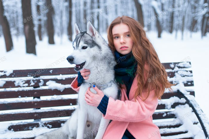 Woman sitting on the bench with siberian husky