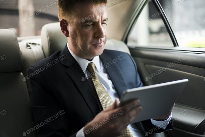 Businessman using a tablet in a car