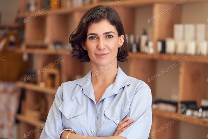 Portrait Of Female Owner Of Gift Store Standing In Front Of Shelves With Cosmetics And Candles