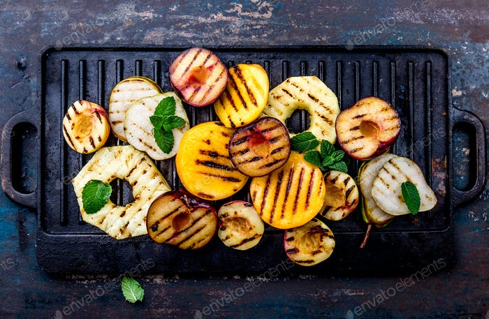 Grilled Fruits - Pineapple, peaches, plums, avocado pear on black cast iron grill pan