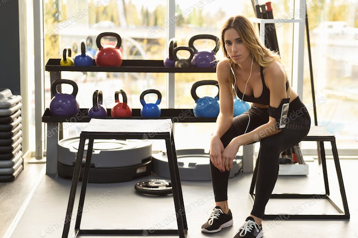 Young woman listening to music with smartphone sitting at gym