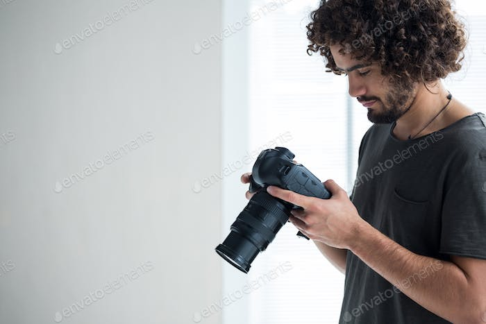 Male photographer reviewing captured photos in his digital camera