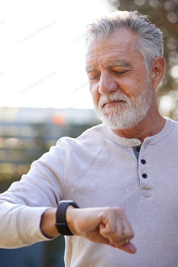 Senior Hispanic Man Checking Health Monitor On Smart Watch In Garden At Home