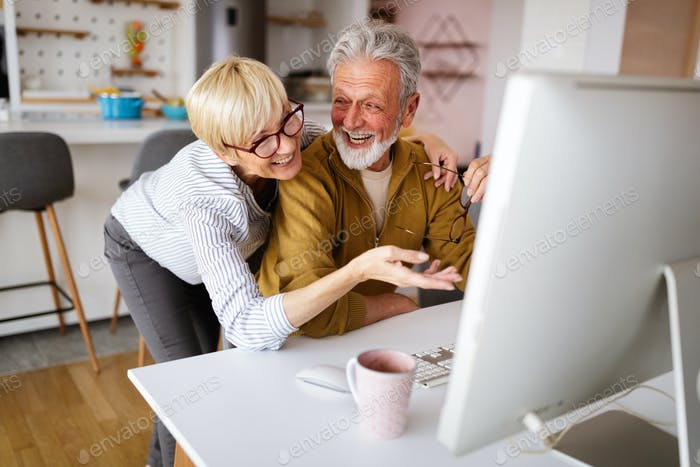Senior retired couple learn about computer and online support