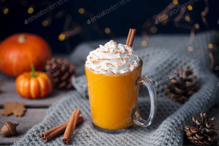 Pumpkin Latte with Spices. Boozy Cocktail with Whipped Cream on top on a Grey Background