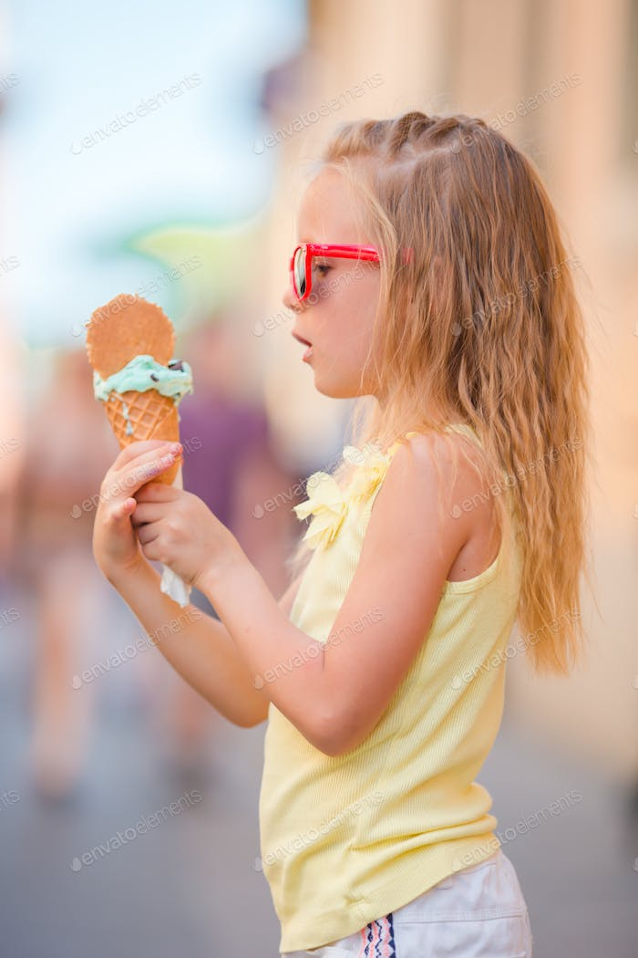 Adorable little girl eating ice-cream outdoors at summer. Cute kid enjoying real italian gelato near
