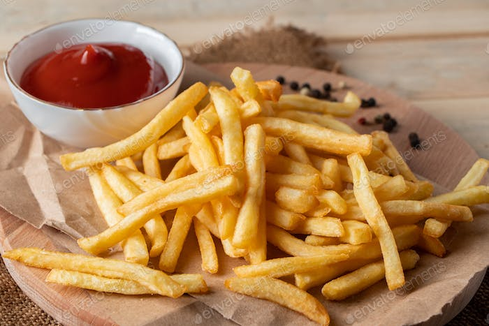 Hot golden french fries with sauce on wooden background. Homemade rustic food.