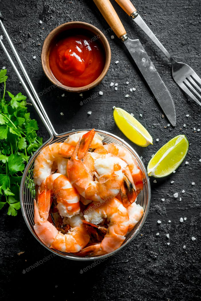 Delicious shrimps in a colander with lime slices, sauce and parsley.