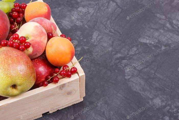 Frische reife Früchte in Holzkiste. Lebensmittel mit gesunden Mineralien und Vitaminen. Platz für Text