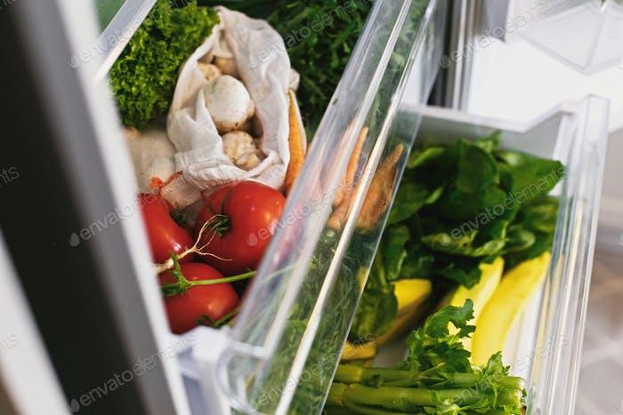 Zero waste grocery in fridge. Fresh vegetables in opened drawer in refrigerator