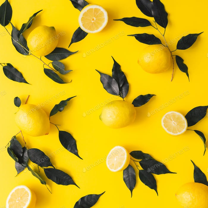 Creative summer pattern made of lemons and black leaves on yellow background. Fruit minimal