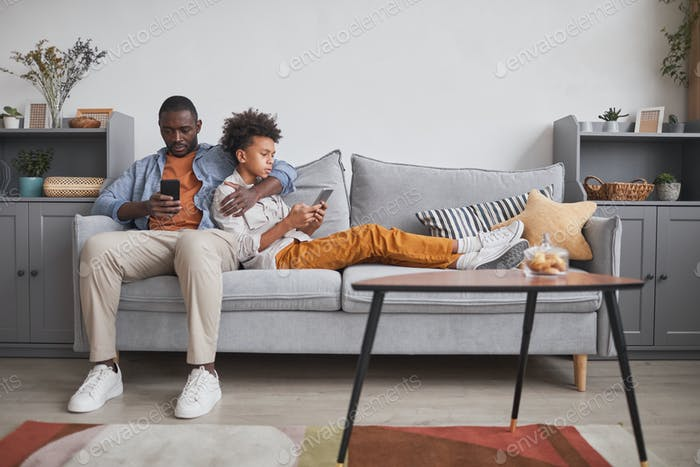 Man and Teen Son with Smartphones