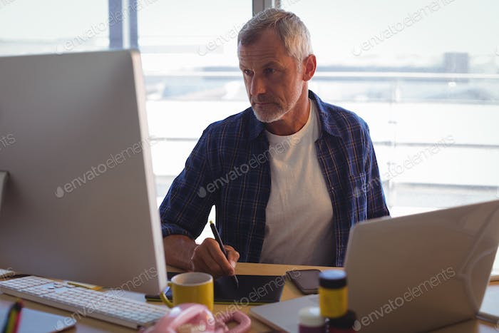 Serious businessman working on digitizer at office desk
