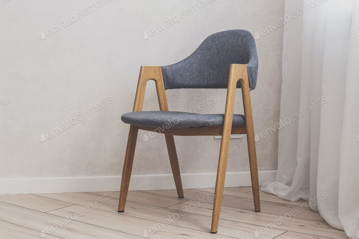 Modern grey chair with white brick walls on background and wood floor