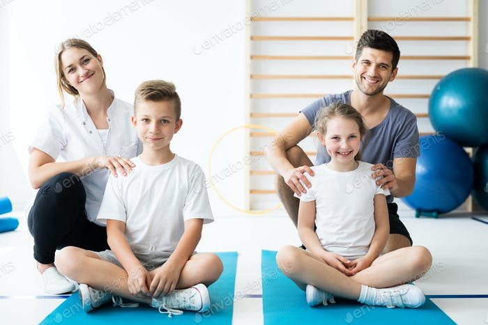 Kids sitting on blue yoga mats with their professional physician