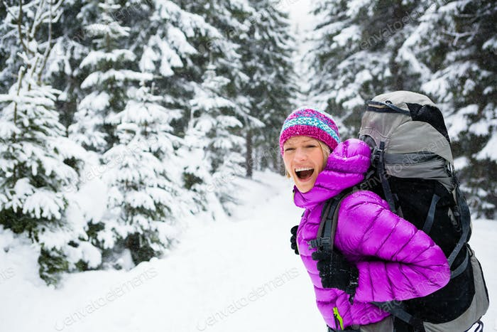 Happy woman walking in winter forest with backpack