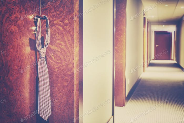 Vintage stylized tie hanging on a hotel closed door handle