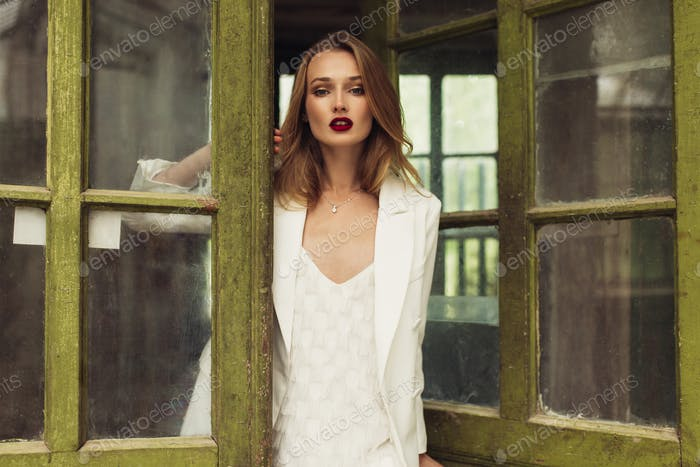 Young gorgeous pensive woman in white jacket and dress thoughtfu