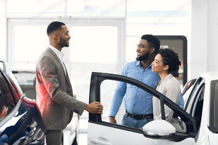 Car Seller Consulting Buyers Showing Luxury Auto In Dealership Shop